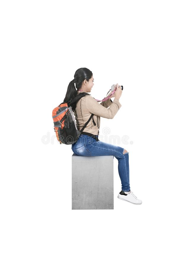 Asian woman with a backpack sitting and holding a camera to take pictures royalty free stock photography