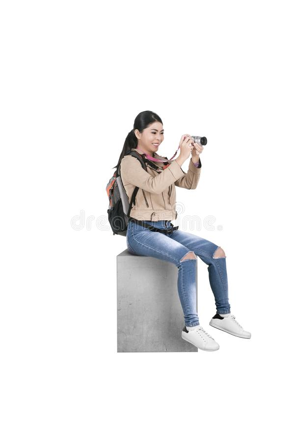 Asian woman with a backpack sitting and holding a camera to take pictures stock photo