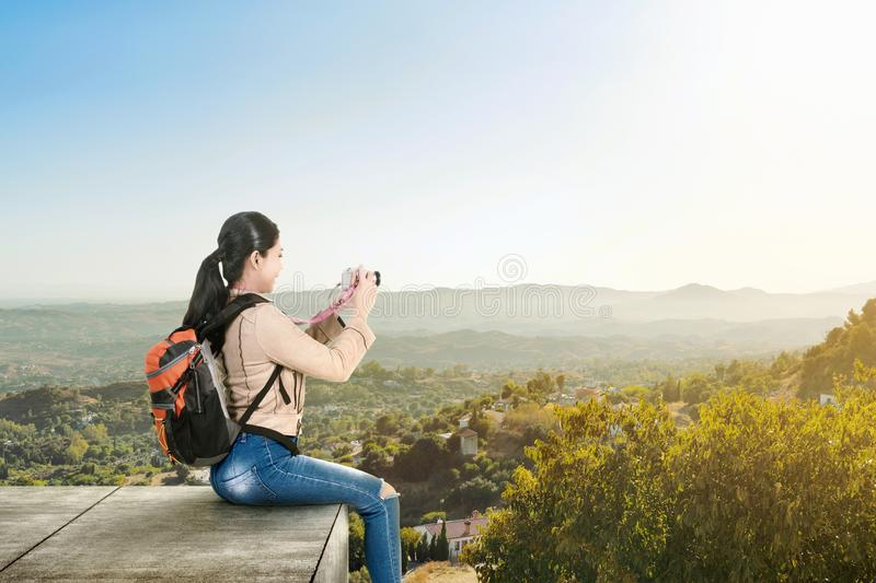 Asian woman with a backpack sitting on the rooftop and holding a camera to take pictures stock photo