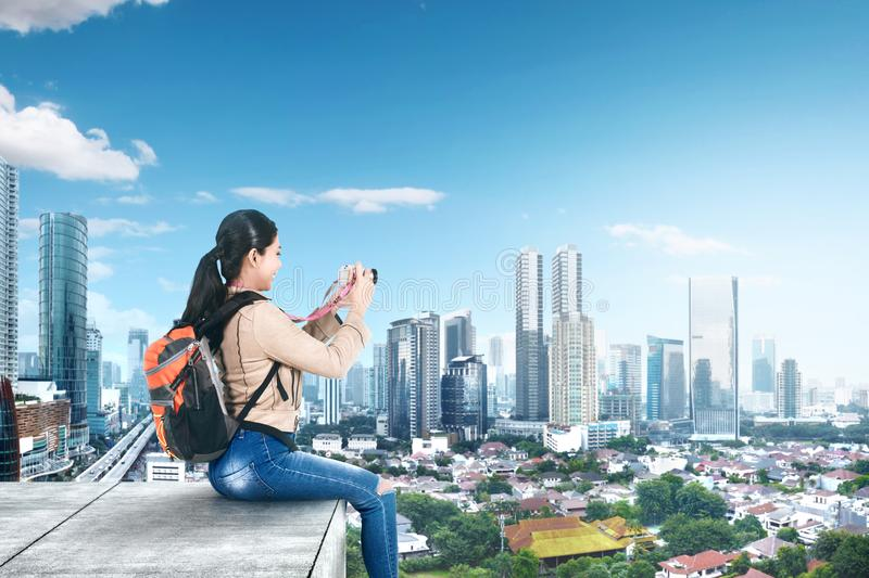 Asian woman with a backpack sitting on the rooftop and holding a camera to take pictures stock photos