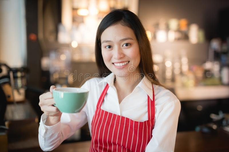 Asian woman barista smiling with a cup of coffee in her hand,Coffee salesmen deliver coffee to customers,vintage filter effect. Asian woman barista smiling with stock photography
