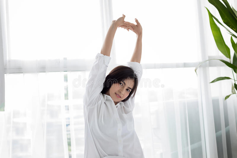 Asian woman Beautiful young smiling woman sitting on bed and stretching in the morning at bedroom after waking up in her bed full stock photos