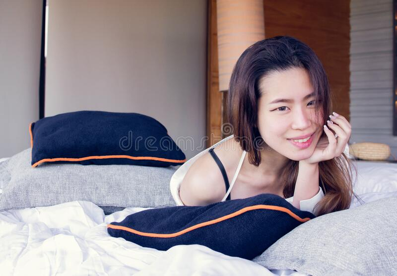 Asian woman on bed in the morning royalty free stock photography