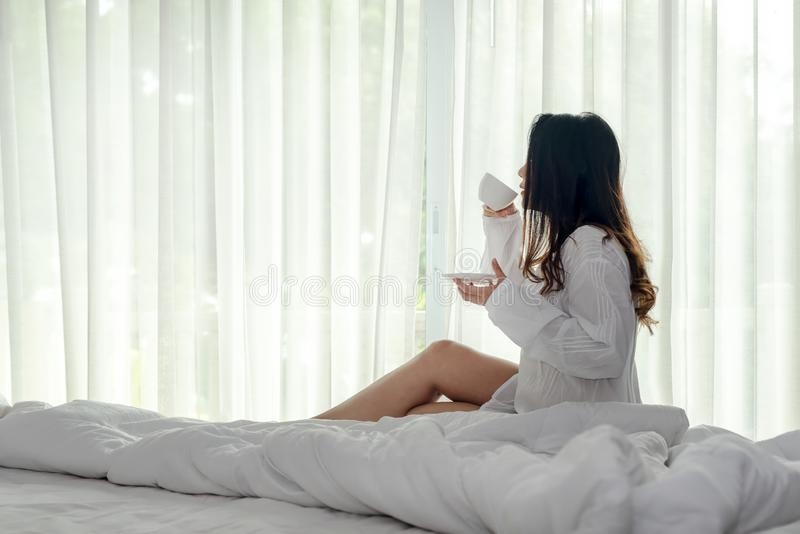 Asian woman in bedroom drinking coffee after wake up and relax mood in holiday near window, sunny morning. royalty free stock photography