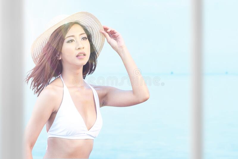 Asian woman with bikini and hat relaxing royalty free stock photos