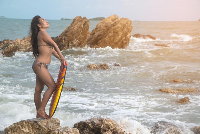 An Asian woman in a bikini is standing holding a surf board on the beach. stock image