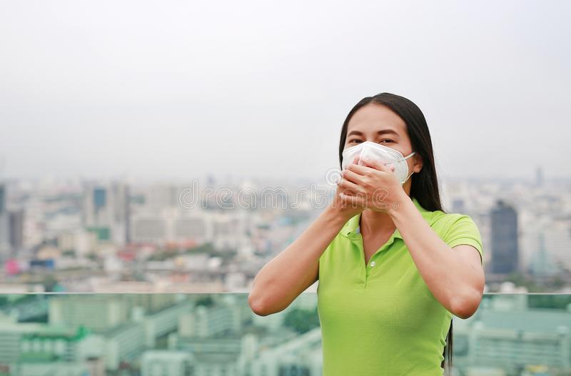 Asian woman breathing by wearing a protection mask against PM 2.5 air pollution in Bangkok city. Thailand royalty free stock photo