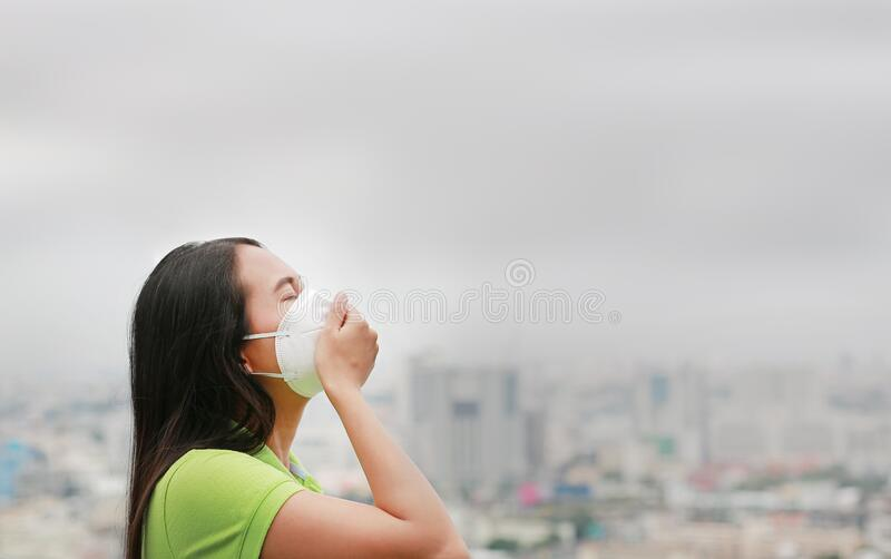 Asian woman breathing by wearing a protection mask against PM 2.5 air pollution in Bangkok city. Thailand royalty free stock image