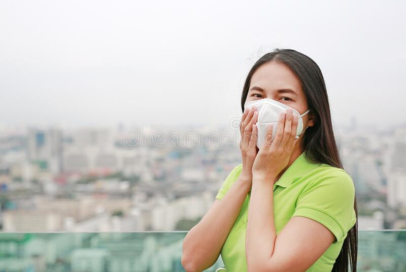 Asian woman breathing by wearing a protection mask against PM 2.5 air pollution in Bangkok city. Thailand stock photos