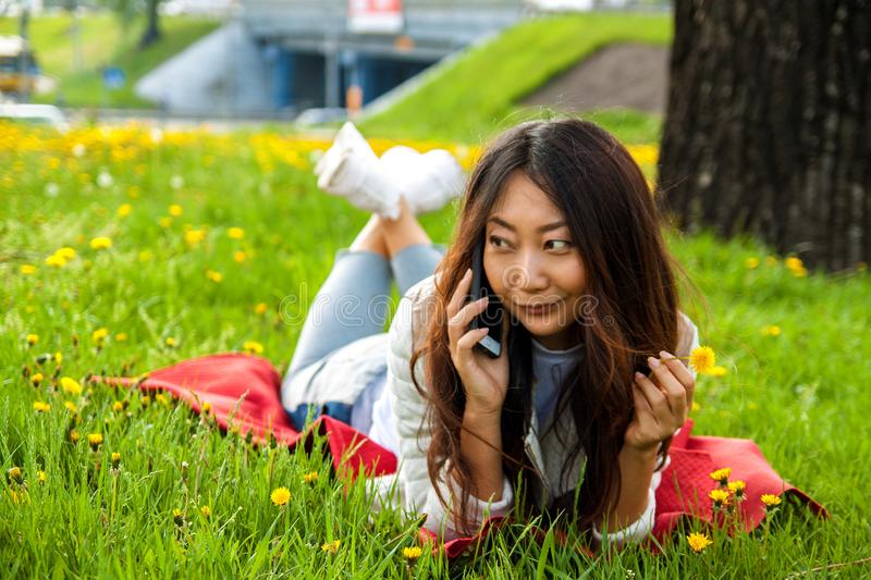 Asian woman calling by phone in summer park on green grass. Asian happy woman calling by phone in summer park on green grass stock photo