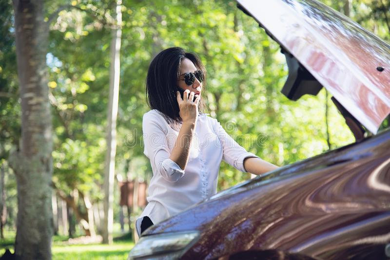 Asian woman calling repairman or insurance staff to fix a car engine problem on a local road stock images
