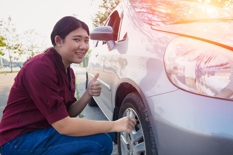 Asian women car tire air check for good pressure. Asian woman car tire air check for good pressure before go trip royalty free stock photography