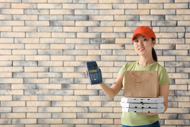 Asian woman with cardboard pizza boxes, paper bag and bank terminal on brick wall background. Food delivery service stock photography