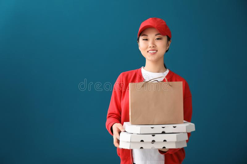 Asian woman with cardboard pizza boxes and paper bag on color background. Food delivery service royalty free stock image