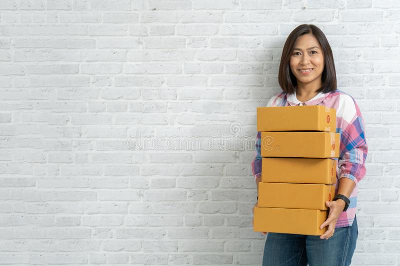 Asian woman carry brown parcel or cardboard boxes on brick wall royalty free stock photos