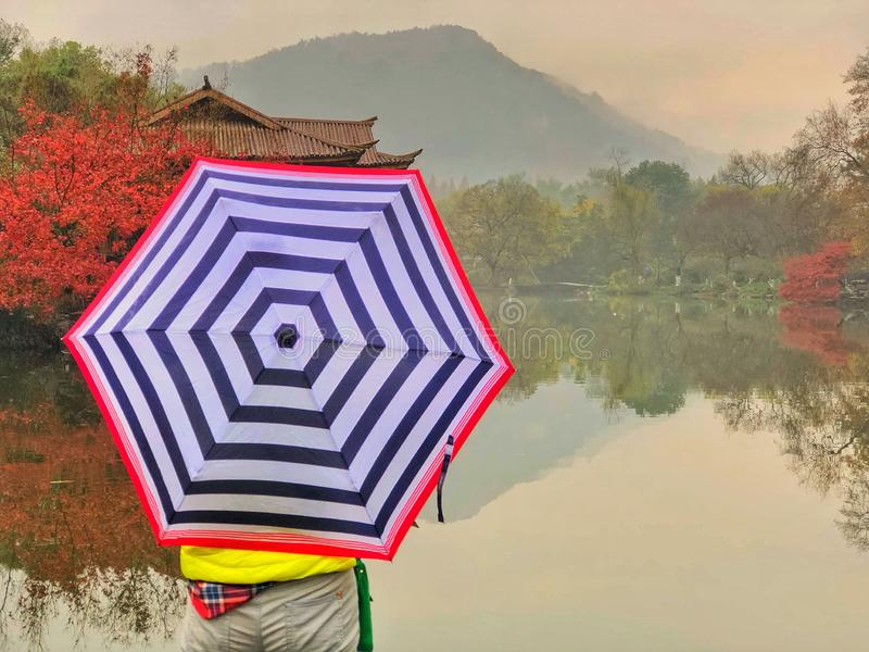 Asian woman carry the umbrella standing in front of the mountain which has a mirror reflection on the river and maple trees. Asian woman carry the umbrella royalty free stock photos