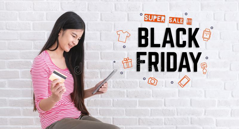 Asian woman in casual cloth holding credit card and using to online shopping in black friday sale with tablet at white brick wall royalty free stock image