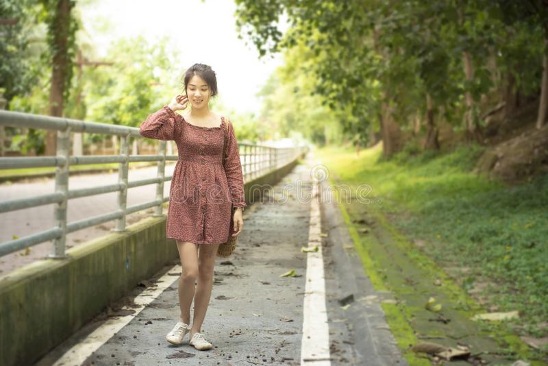 Asian woman in casual dress walk with smile on footpath in outdoor park and copy space with blur of background,vintage style.  stock photography