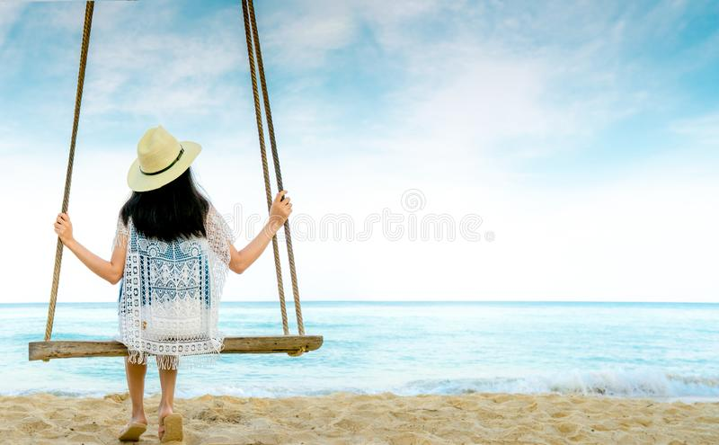 Asian woman in casual style wear hat and sandals sit on swings at sand beach and looking beautiful tropical paradise sea and sky. royalty free stock image