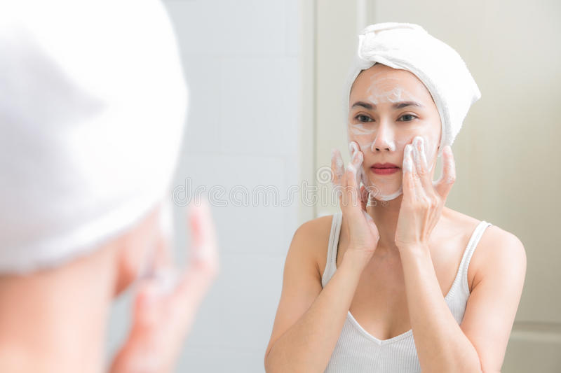 Asian woman cleaning face skin enjoy herself with bubble cleansing foam. stock images