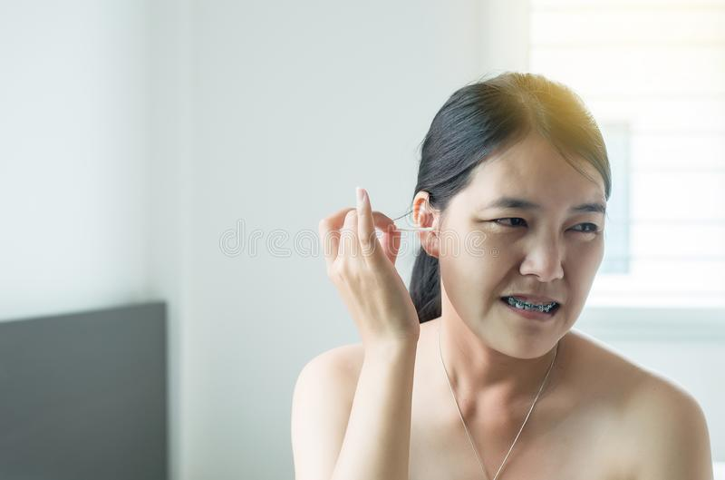 Asian woman cleaning her ears with cotton bud in bed,Female using cotton stick. Asian woman cleaning her ears with cotton bud in bedroom,Female using cotton royalty free stock images