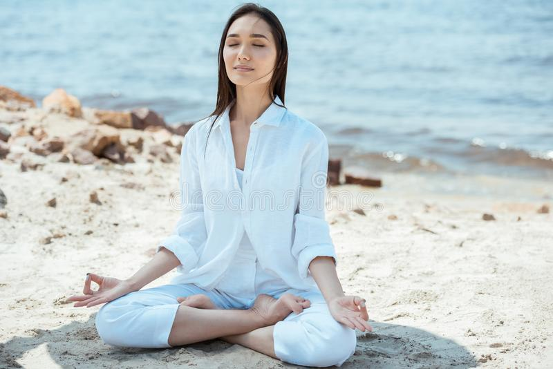 asian woman with closed eyes meditating with akash mudra gesture in lotus position stock images