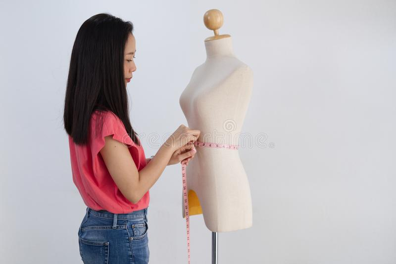 Asian woman cloth designer measuring waist of female mannequin on white back ground. royalty free stock images