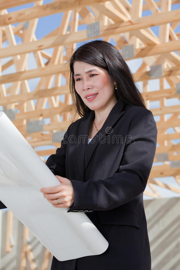 Asian Woman Contractor. Reviewing a set of plans on a job site. New home construction stock photography