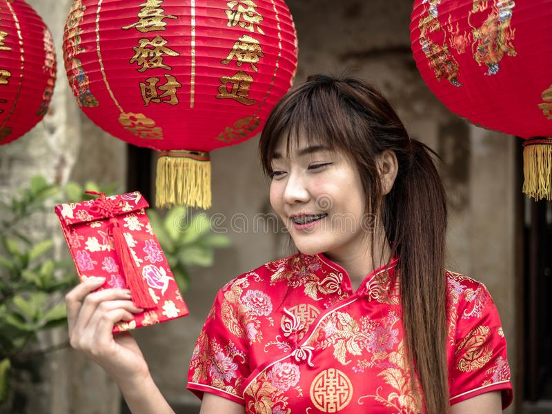 Asian woman on a costume festival holding a red pocket - lucky money. Tet holiday. Chinese New Year stock photo