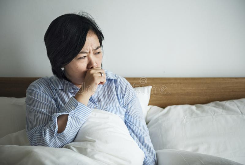 Asian woman coughing in the bed royalty free stock images