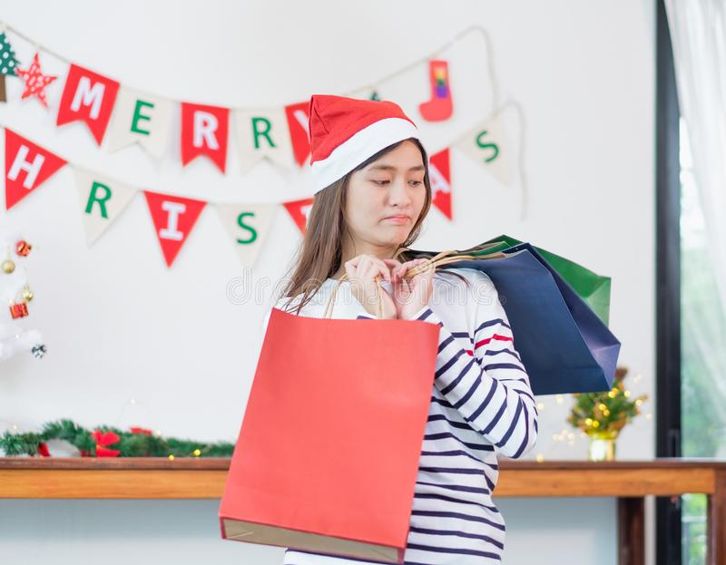 Asian woman disappointed about payment when buy a lot of christmas gift in shopping bags,upset expenses after shopping royalty free stock photo