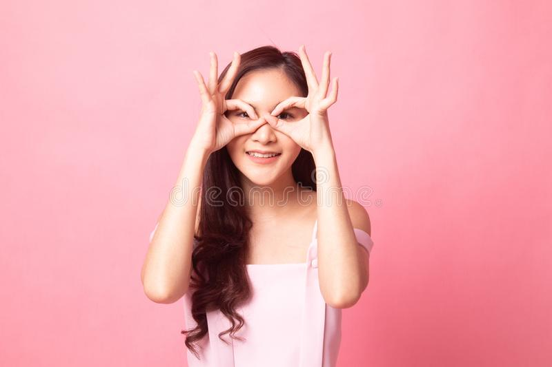 Asian woman do funny double OK sign as glasses. On pink background royalty free stock photo