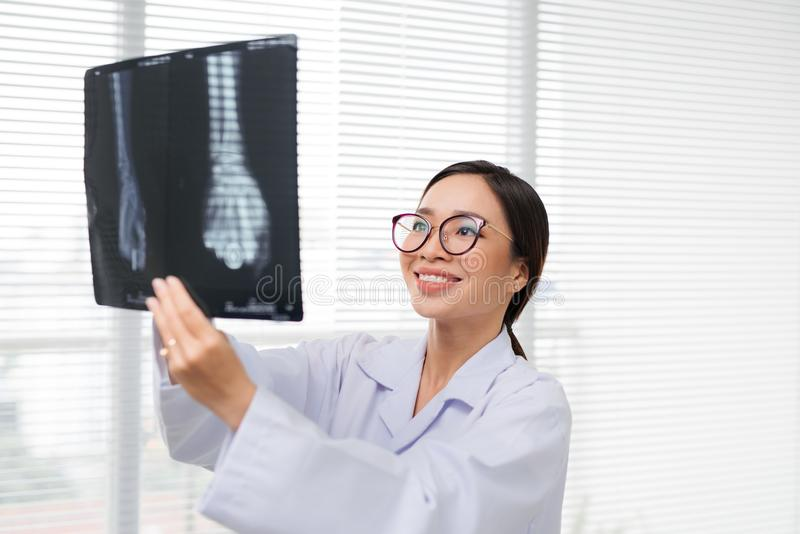 Asian woman doctor in hospital looking at x-ray film healthcare royalty free stock images