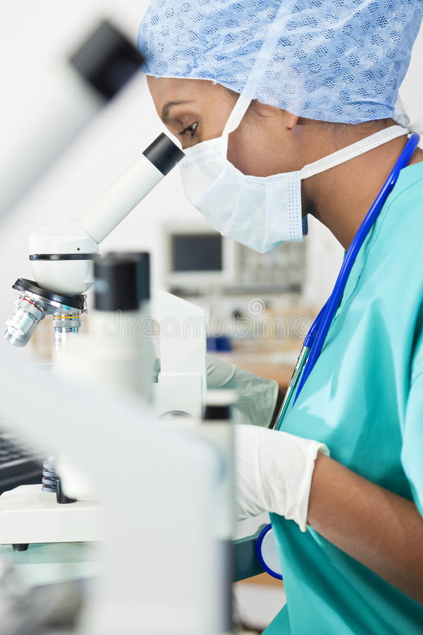 Asian Woman Doctor or Scientist Using a Microscope. An Asian female medical doctor or scientific researcher using her microscope in a laboratory royalty free stock photography