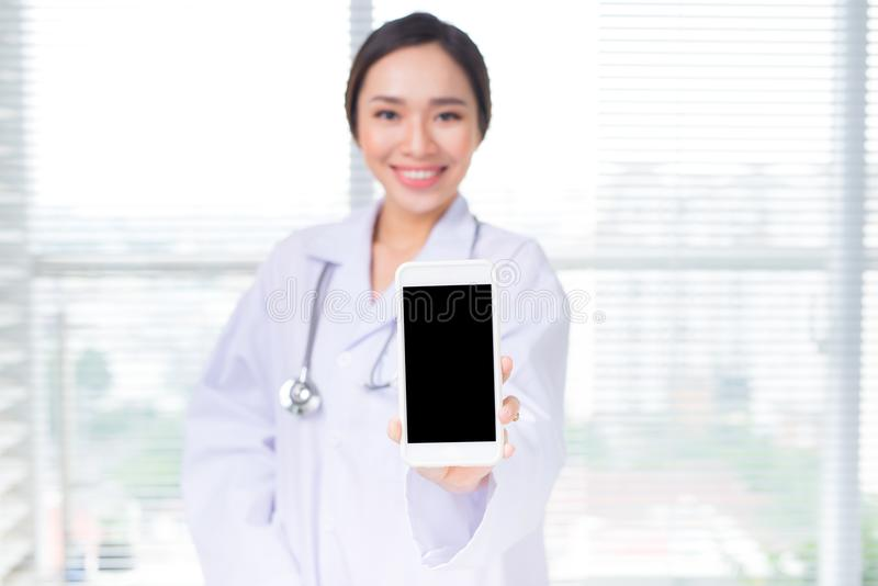 Asian woman doctor showing a smartphone screen.  stock image