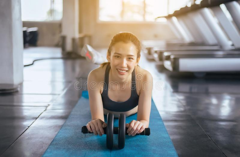 Asian woman doing workout and exercise with roller wheel,Individual sport,Hppy and smiling stock photo