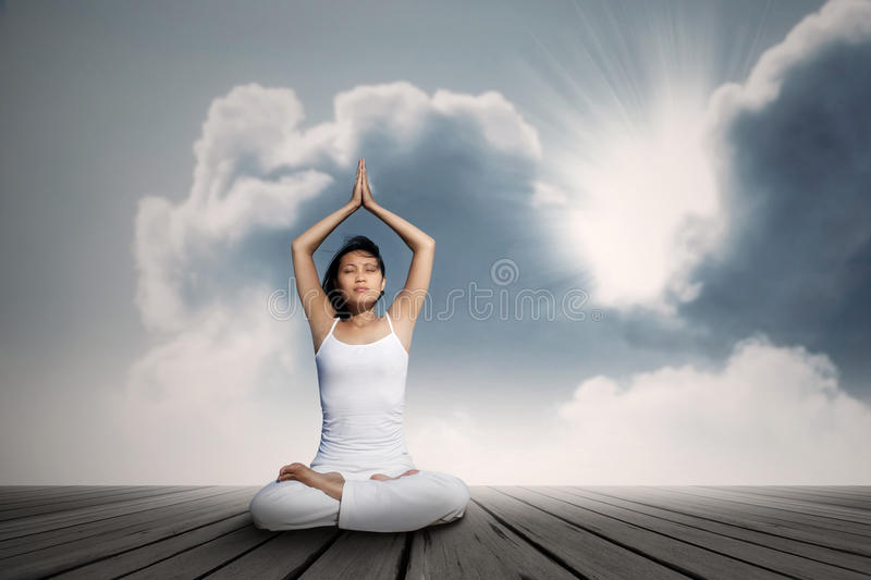 Asian woman doing yoga exercise under blue sky. Young asian woman doing yoga exercise under blue sky stock photography