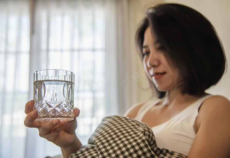 Asian woman drink water after wake up in the morning sitting on a bed royalty free stock image