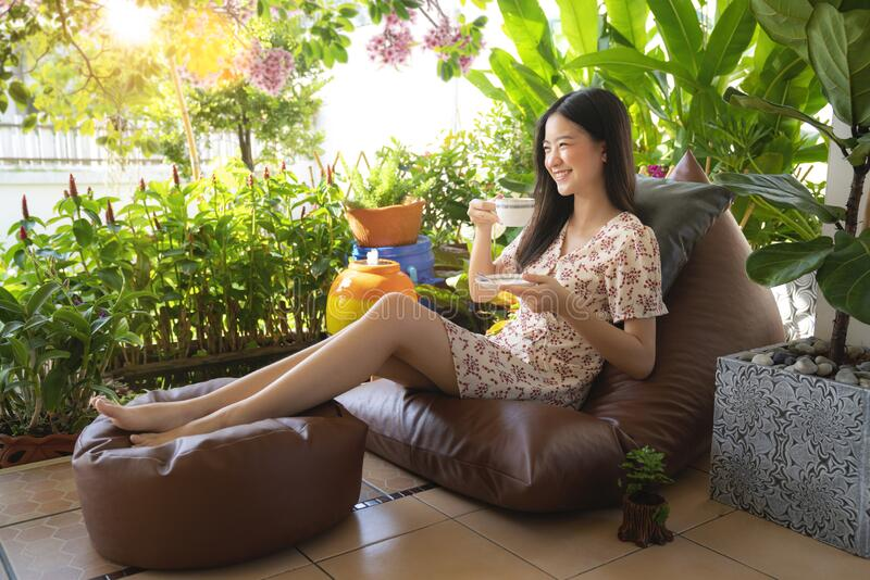 Asian woman drinking a cup of coffee and enjoy nature view stock image