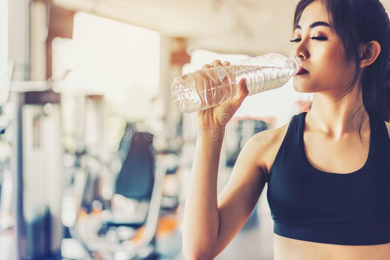 Asian woman drinking pure drinking water for freshness after workout or exercise training in fitness gym with fitness equipment b royalty free stock photo