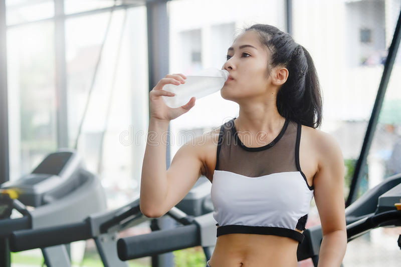 Asian woman drinking water on wellness. Asian woman drinking water on wellness in sport gym stock photography