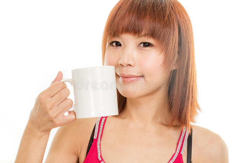 Asian woman drinking from white coffee cup royalty free stock image