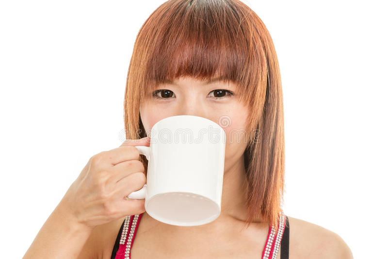 Asian woman drinking from white coffee cup stock images