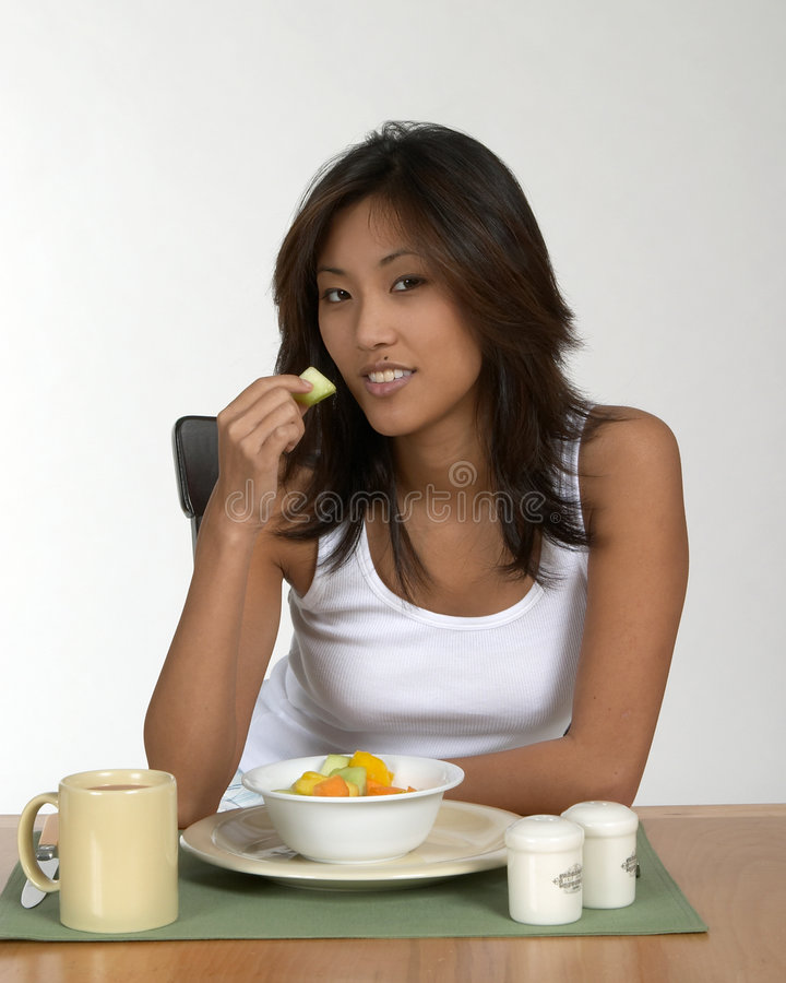 Asian woman eating fruit stock images