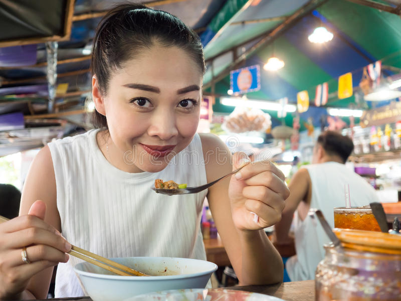 Asian woman eating noodle in Thai local restaurant. Asian woman eating noodle in Thai local restaurant in Thailand royalty free stock image
