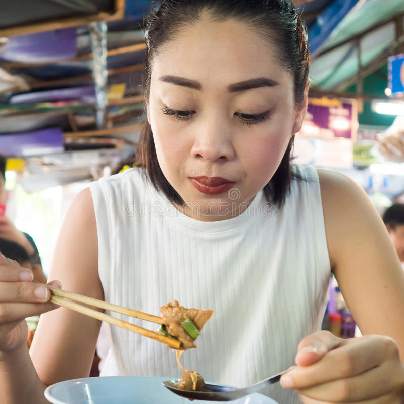Asian woman eating noodle in Thai local restaurant. Asian woman eating noodle in Thai local restaurant in Thailand stock image