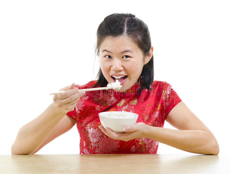 Asian woman eating rice. With chopsticks over white background royalty free stock photography