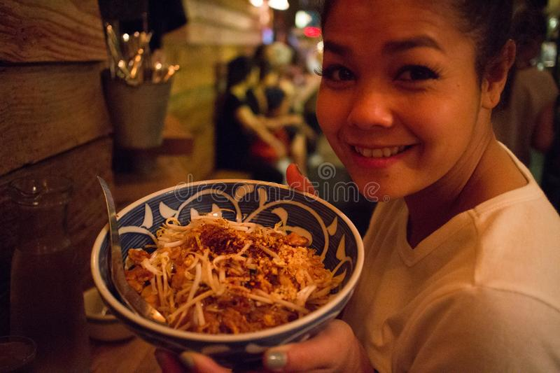 Asian Girl with a Bowl of Pad Thai at a Thai Restaurant in New York City. An asian woman eats a bowl of Pad Thai at Pure Thai Cookhouse in Hell`s Kitchen in stock photo