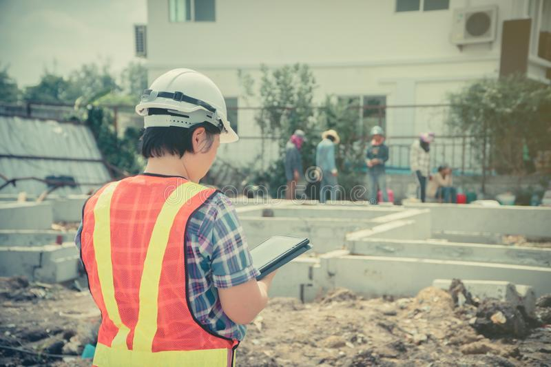 Asian women engineering holds a tablet for use in the inspection of construction sites for accuracy and in accordance with the pla stock photo