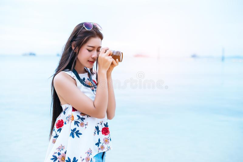 Asian woman enjoy take photo by digital camera at beach. Single and lonely woman concept. Happiness and Lifestyle concept. Beauty. And Nature theme. Ocean and royalty free stock image